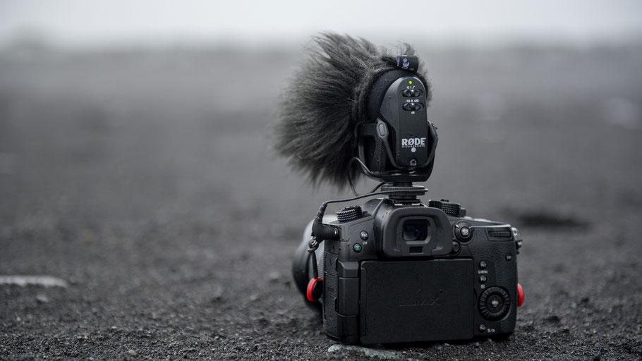 Kamera auf schwarzem Vulkansand in Island. Bild von Ricky Kharawala auf Unsplash.