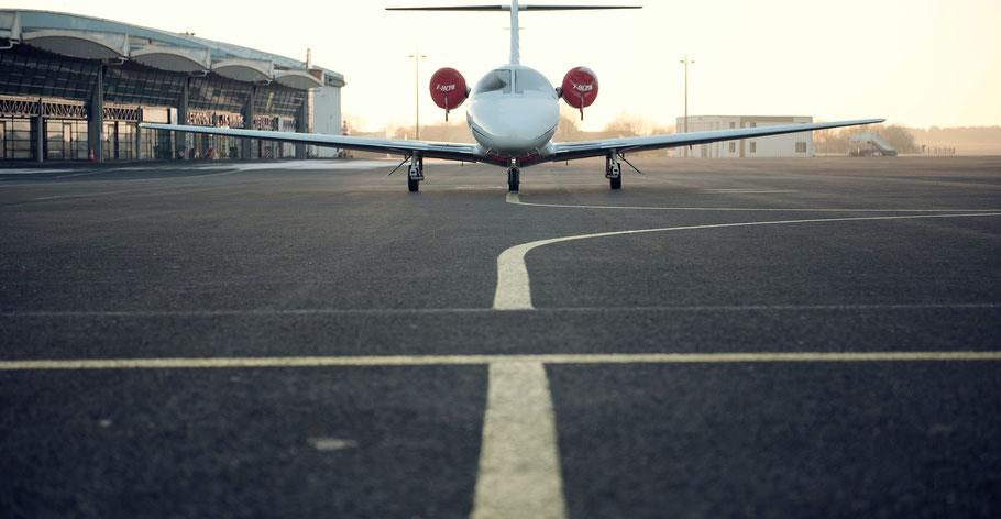 Ein Flugzeug steht vor einem Flughafengebäude. Bild von Marcus Zymmer auf Unsplash.