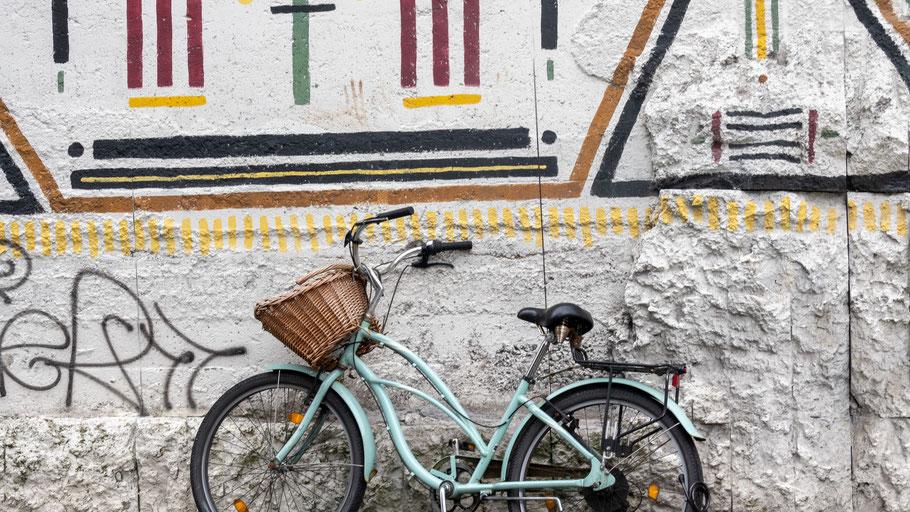 Türkisfarbenes Fahrrad vor einer Wand mit Graffiti. Bild von Steve Smith auf Unsplash.