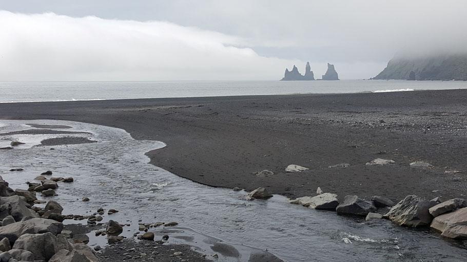 Blick vom schwarzen Sandstrand auf das Meer. Bild von Tomasz Tomczak auf Unsplash.