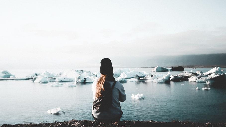 Eine junge Frau sitzt mit dem Rücken zum Betrachter an einem Gletschersee. Bild von Martin Balle auf Unsplash.