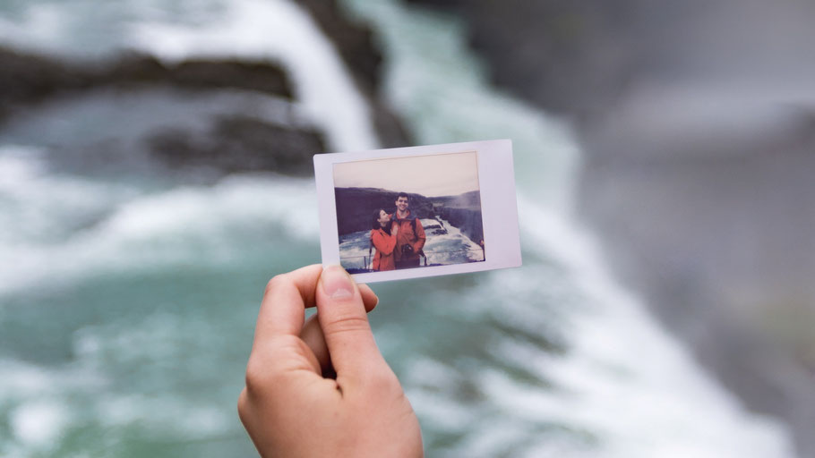 Frauenhand hält Foto von Touristenpaar hoch. Bild von Theodor Vasile auf Unsplash.