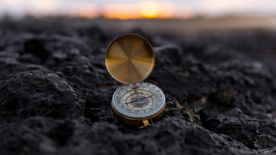 Kompass auf schwarzem Sandstrand in Island. Bild von Dunamis Church auf Unsplash.
