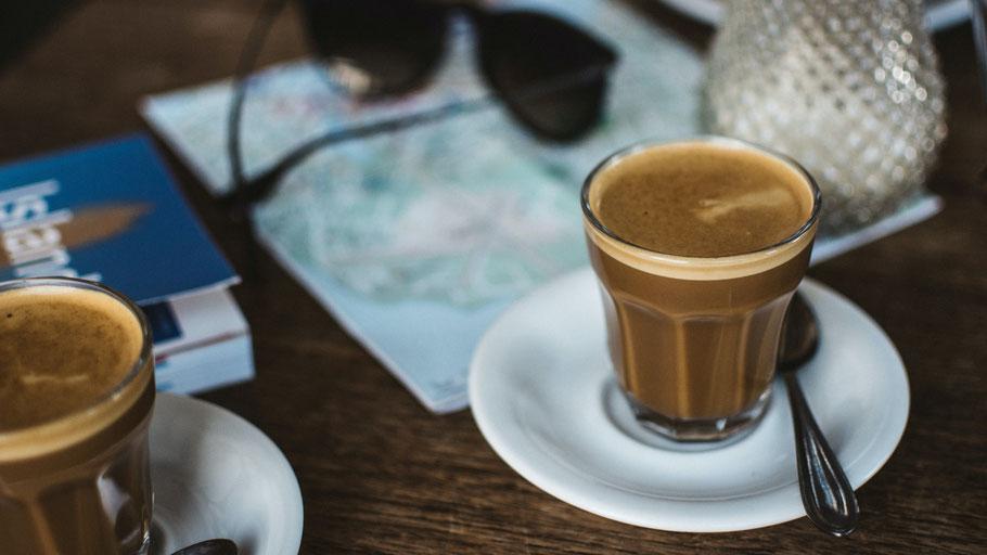 Zwei Kaffeetassen plus Island-Karte. Bild von Jakub Kapusnak auf Unsplash.