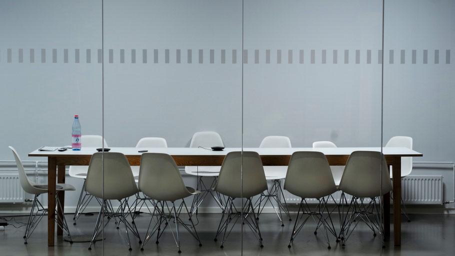 Konferenztisch mit leeren Stühlen. Bild von Pawel Chu auf Unsplash.