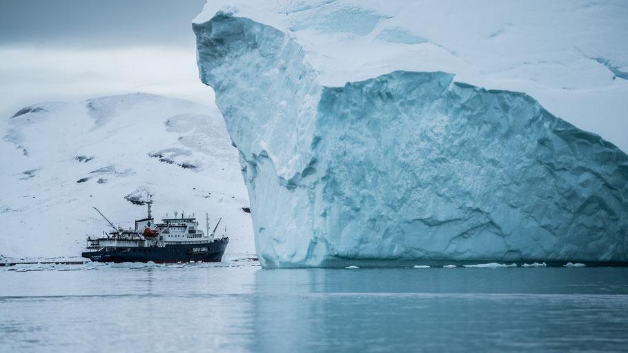 Schiff an einem Eisberg in der Arktis. Bild von Hubert Neufeld auf Unsplash.