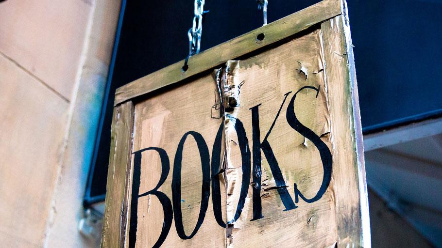Altes Werbeschild eines Buchladens. Bild von César Viteri auf Unsplash.