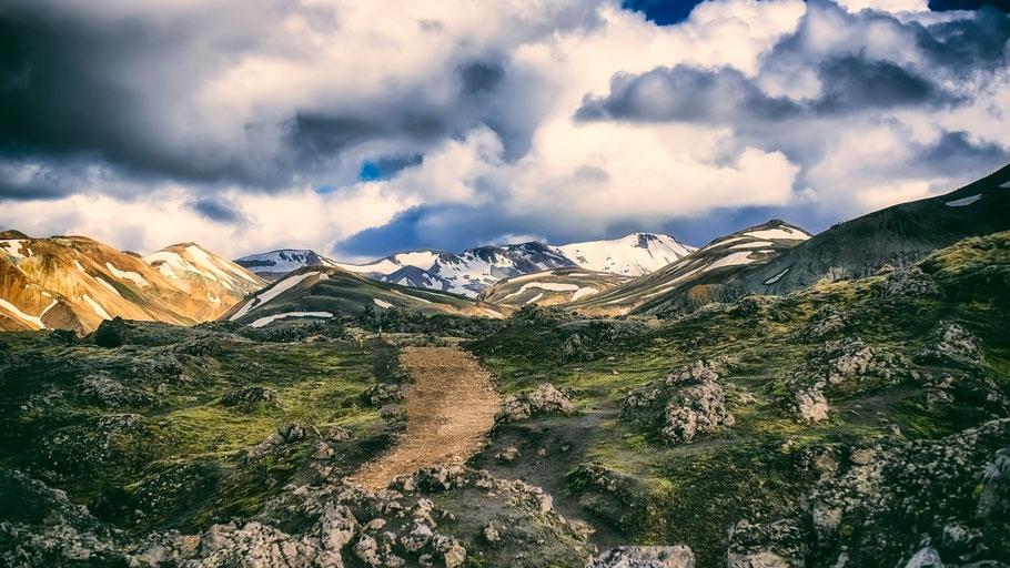Wanderweg durch grüne Hügel mit schneebedeckten Bergen im Hintergrund. Bild von David Mark auf Pixabay.