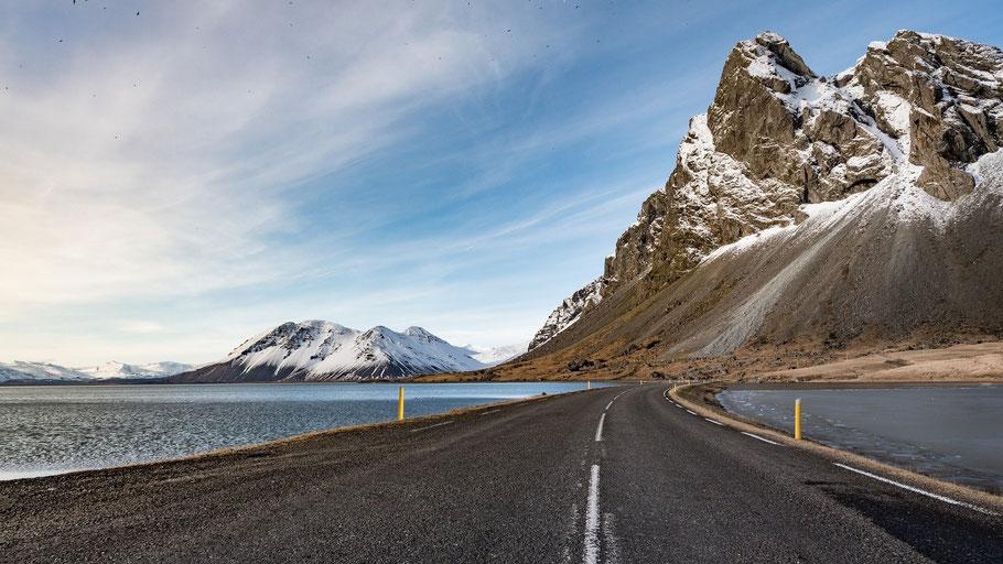 Straße am Wasser, die zu Bergen führt. Bild von Ludovic Chalet auf Pixabay.