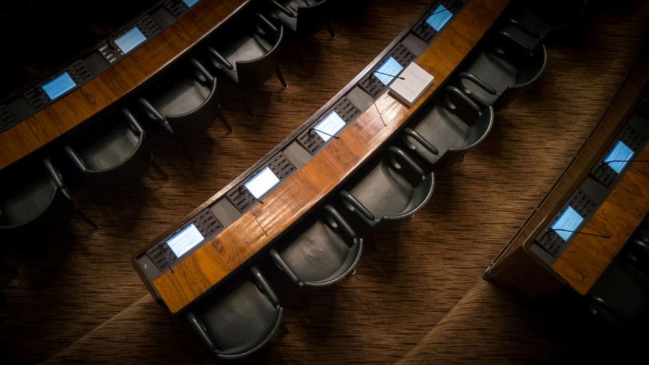 Blick von oben auf Sitzreihen in einem Parlamentssaal. Bild von Joakim Honkasalo auf Unsplash.
