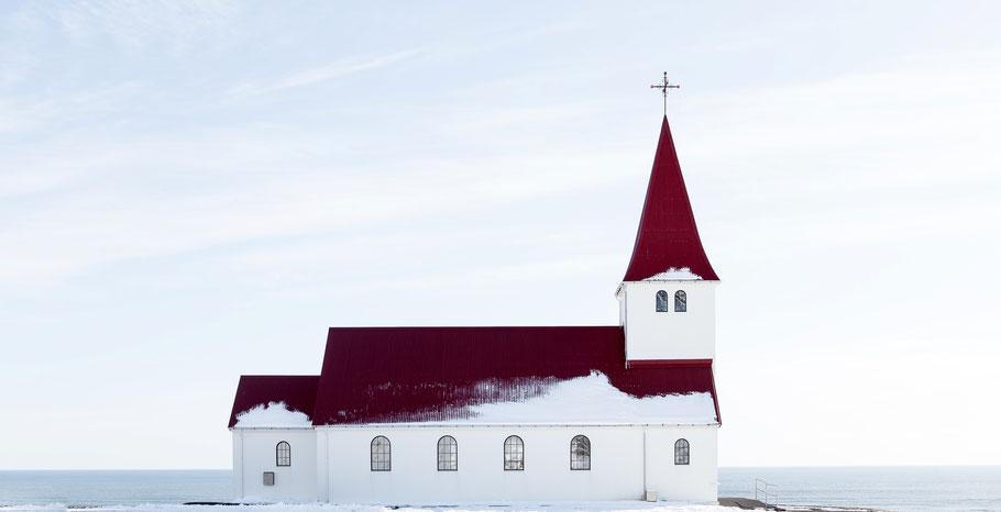 Weiße Kirche mit rotem Dach im Schnee. Bild von Jon Flobrant auf Unsplash.