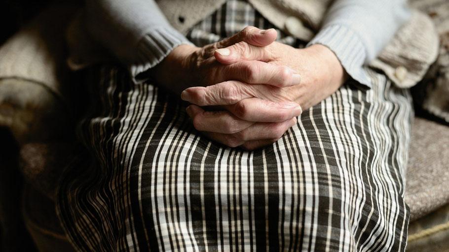 Alte Frau sitzt mit gefalteten Händen auf einem Sessel. Bild von congerdesign auf Pixabay.