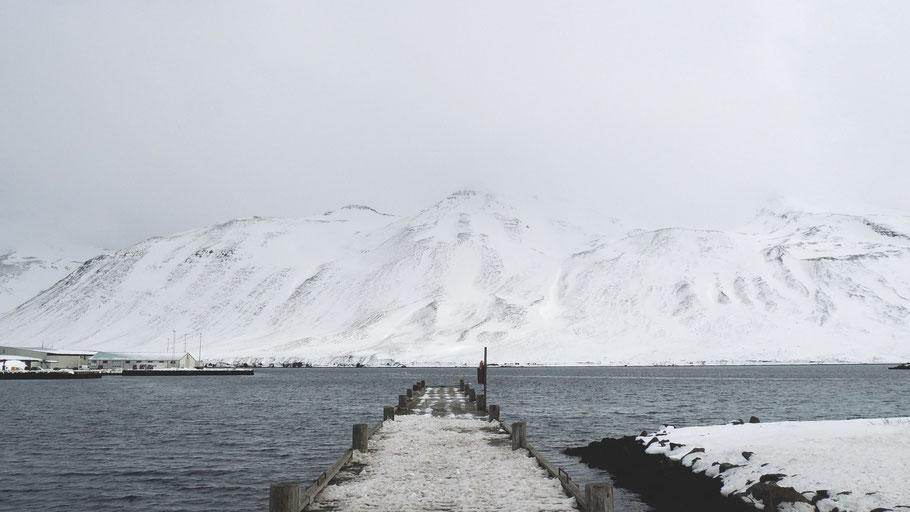 Brücke in Siglufjörður mit Blick auf schneebedeckte Berge. Bild von Luciano Braga auf Unsplash.