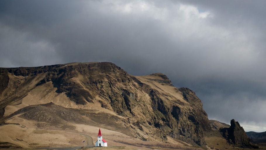 Kirche mit rotem Turm vor Berg. Bild von Tom Archer auf Unsplash.