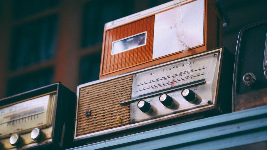 Alte Radiogeräte auf einem Regal. Bild von Igor Ovsyannykov auf Pixabay.
