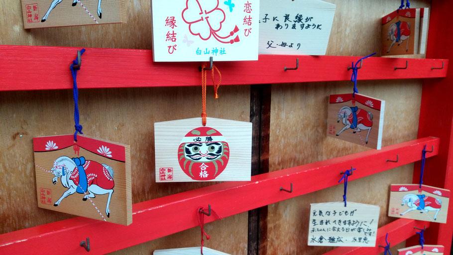 Daruma en un ema a la entrada de un templo en Niigata.