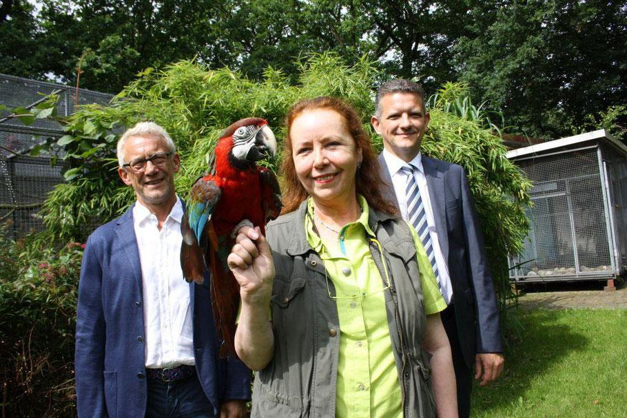 Der Ara Bonito hat es gut: Er ist in der Papageienstation in Hoope aufgewachsen. Die Einrichtung von Margrit Reinhardt erhielt von Uwe Perl (links) und  Andre Niemeyer von der Bremerhavener Tierschutzstiftung Unterstützung. Foto: van Veenendaal