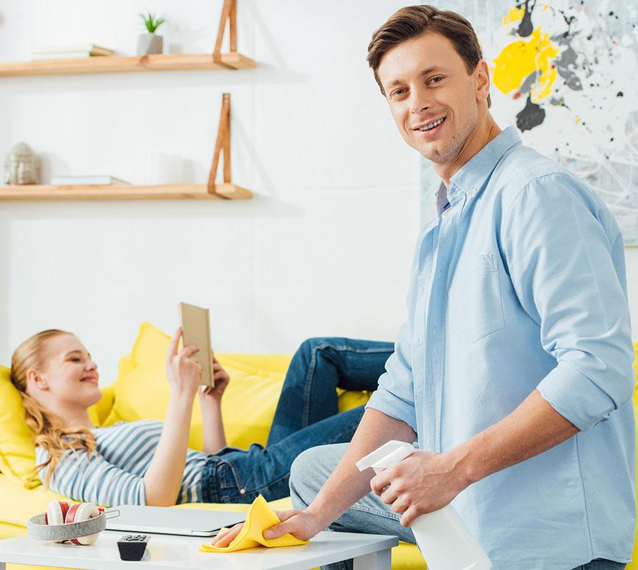Lächelnder Mann mit Laptop entspannt auf der Couch während eine Haushaltshilfe ein Regal wischt