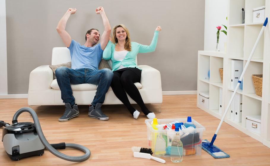 Paar sitzt jubelnd auf der Couch davor liegen Putzutensilien und ein Stausbasuger