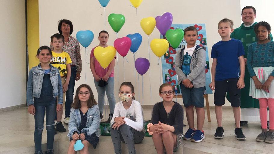 Dorothe Driessen und Pastor Heiko Kiehn überreichten den Kindern zum Start der Vorbereitungen bunte Luftballons