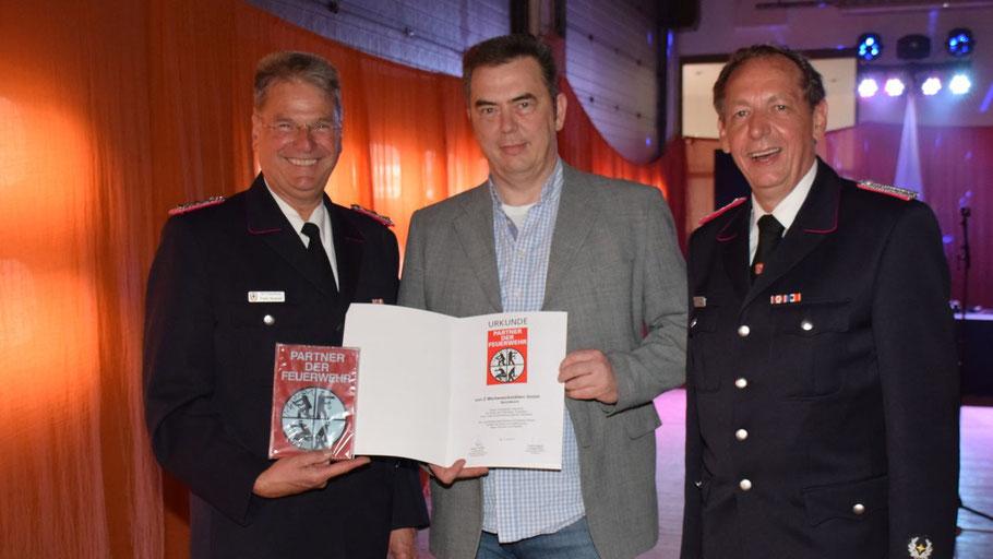 Kreiswehrführer Frank Homrich überreichte die Urkunde an von Z-Geschäftsführer Borris von Zychlinsky. Der Quickborner Wehrführer Wido Schön freute sich mit.