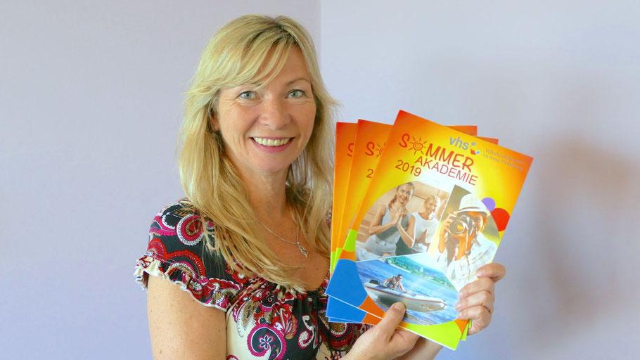 VHS-Leiterin Anette Ehrenstein präsentiert das Programmheft der Sommerakademie, das an vielen Stellen in der Stadt ausliegt