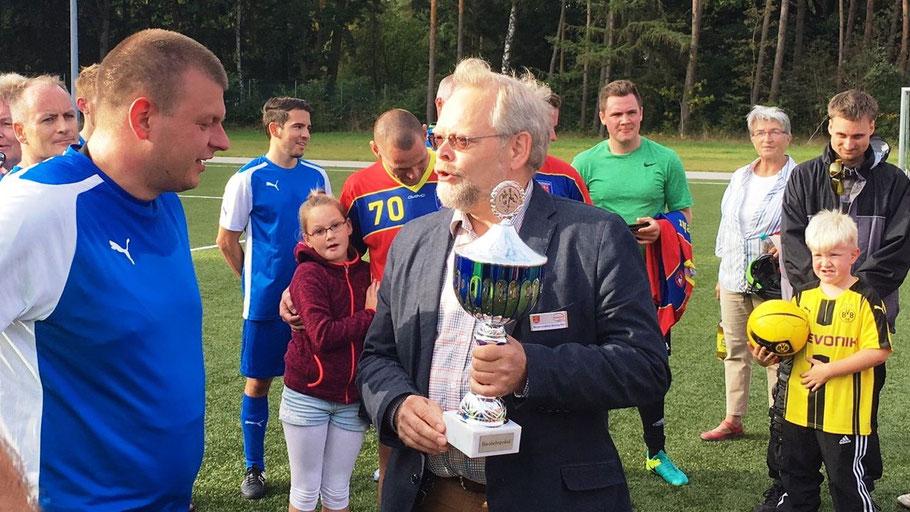Bürgervorsteher Henning Meyn überreichte den Blaulichtpokal an die siegreiche Polizei-Mannschaft