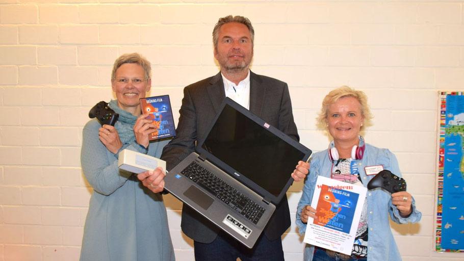 Sie demonstrieren, dass es beim Filmabend um Medien geht: Gudrun Gaden, Jörn Folster und Nicole Eickhoff (v.l.)