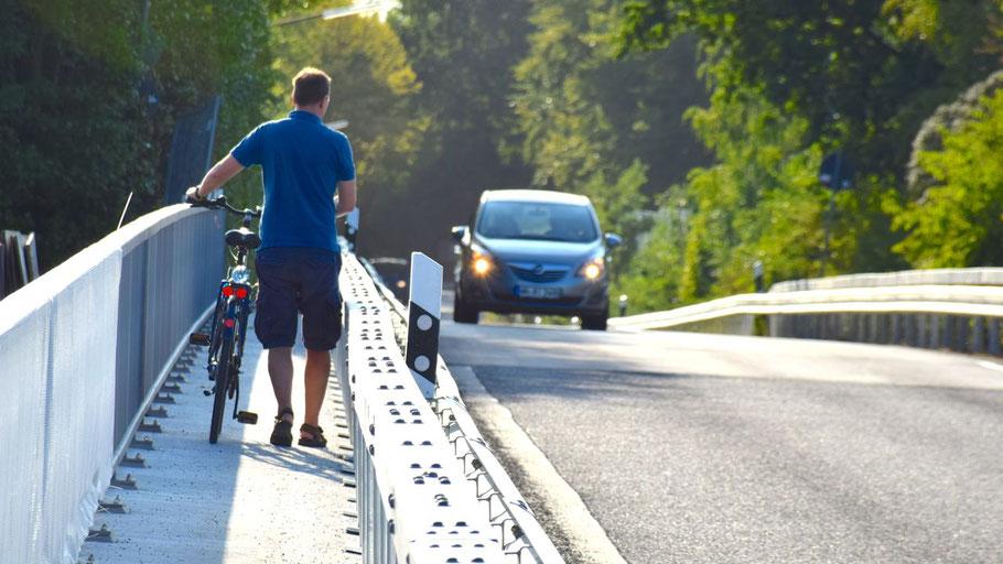 Dieser Radfahrer stieg beim Passieren der Brücke ab, weil er sich unsicher fühlte. Das Foto zeigt, dass zwei Radfahrer auf keinen Fall aneinander vorbei fahren können. Auf der gegenüberliegenden Seite gibt es keinen Geh-/Radweg.