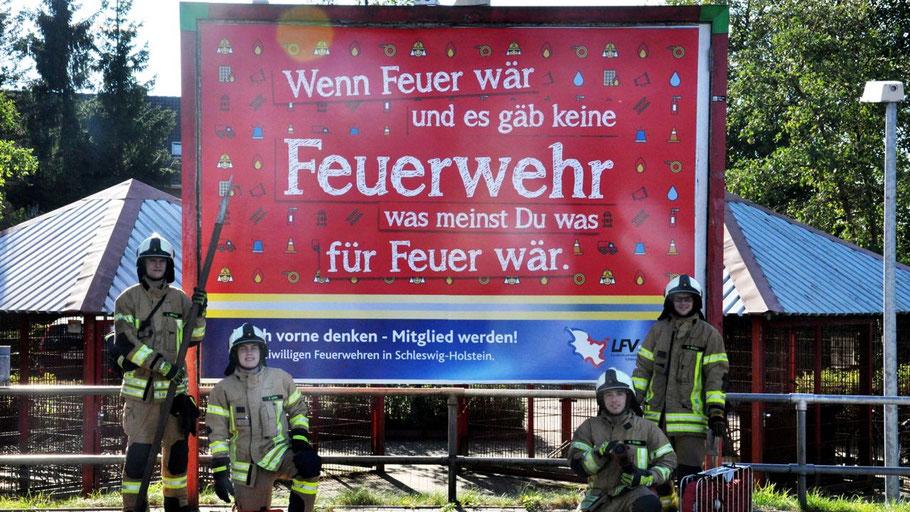 Quickborner Feuerwehrleute präsentieren das Werbeplakat an der AKN-Station Quickborn-Süd.