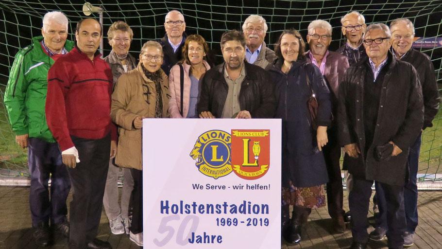 Neben seinen Mitgliedern hatte Lions-Chef Robert Hüneburg (hinter dem Schild) auch TuS-Urgestein Uwe Langeloh (ganz links) und Bauunternehmer Joachim Schaffarzyk (4. v.r.) eingeladen