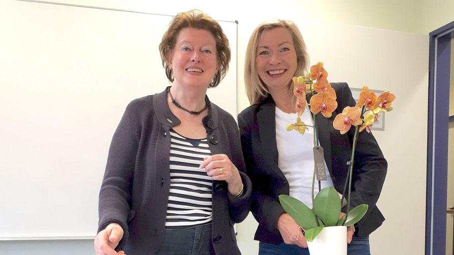 Anette Ehrenstein, Leiterin der VHS Quickborn (re.) überreicht zu Ehren von 40 Jahren Dozententätigkeit an Jeanne Sohn ein Dankeschön des VHS-Teams.
