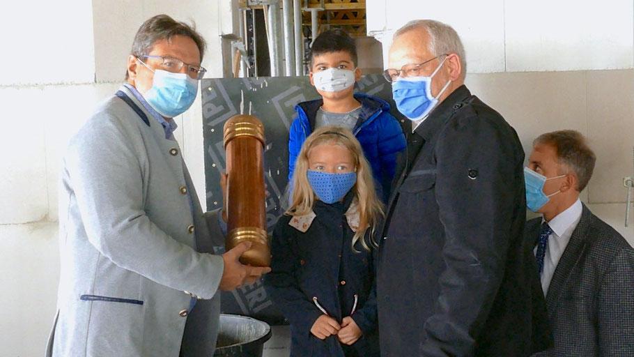 Bürgermeister Thomas Köppl, die Eulenratsmitglieder Tarek und Nele sowie Bürgervorsteher Henning Meyn mauerten unter den Augen von Fachbereichsleiter Helge Maurer die Kapsel ein (v.l.)