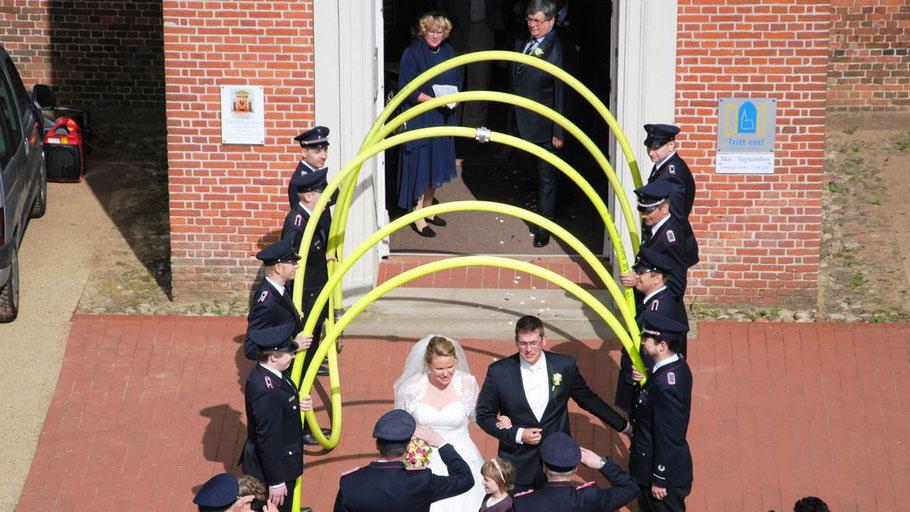 Ein Bogen aus einem Feuerwehrschlauch bildete das stilvolle Ambiente für das Hochzeitspaar