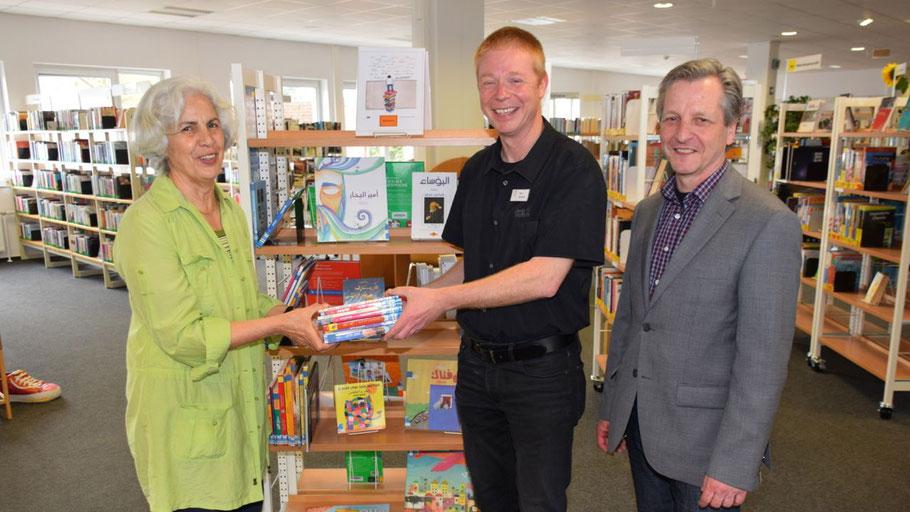 Büchereileiter Klaus Fechner und Fachbereichsleiter Burkhard Arndt (r.) freuen sich über die Bücher in arabischer Sprache, die Naimeh Hollmann der Bücherei schenkte.