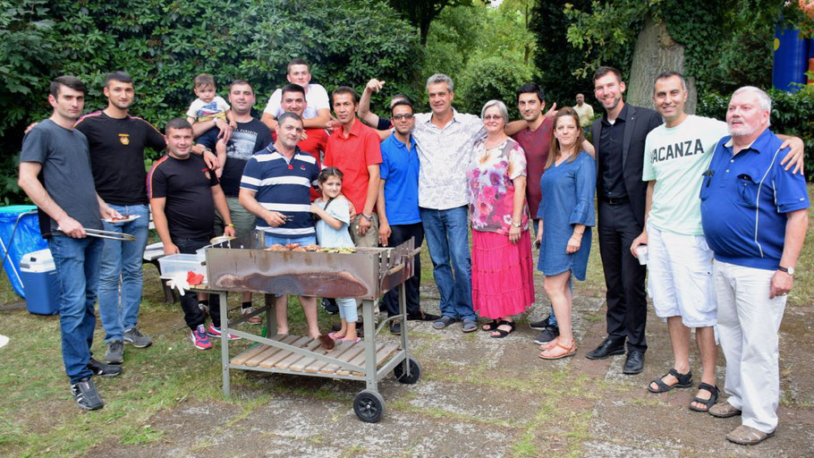 Versammelt am Grill: Einige der Flüchtlinge zusammen mit ehrenamtlichen Betreuern und Betreuerinnen und Hauptamtlichen der Diakonie