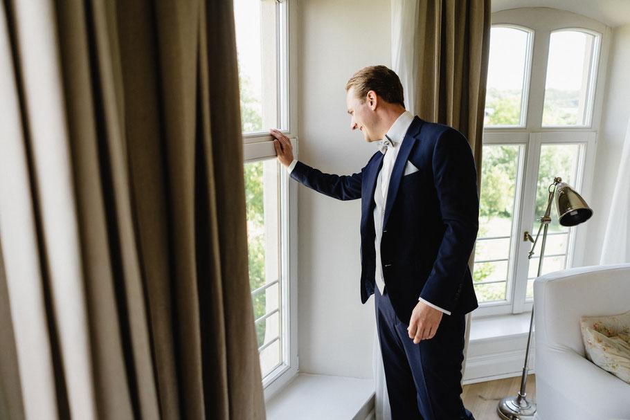Bräutigam schaut aus Fenster Hochzeitsreportage