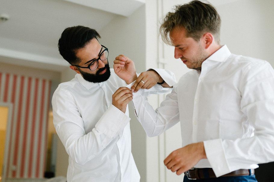 Bräutigam bekommt Unterstützung beim Ankleiden