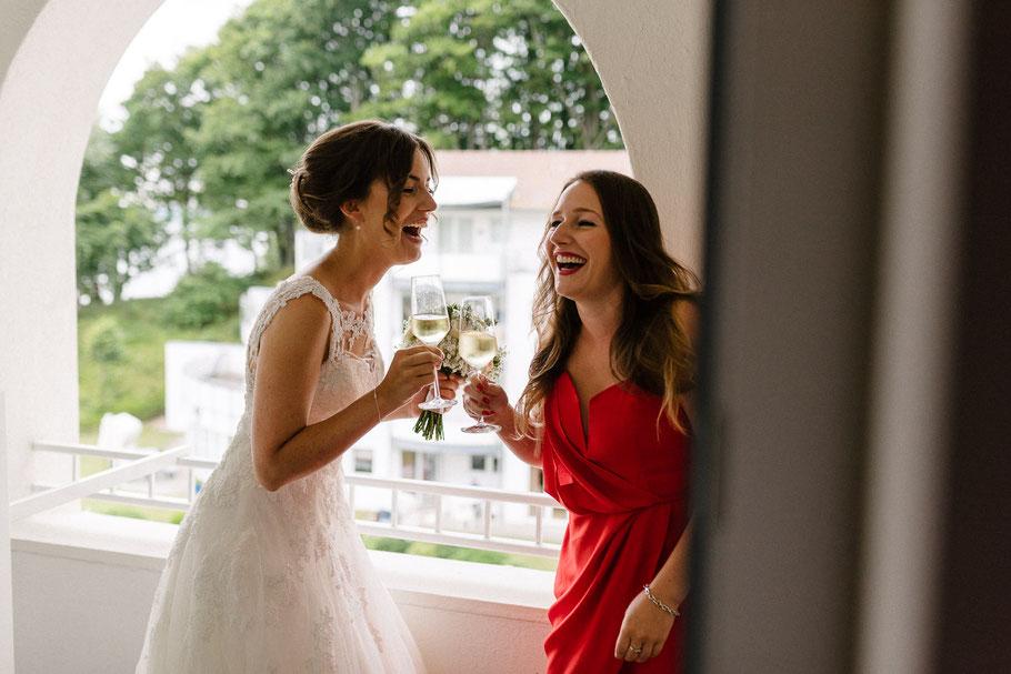 Braut stößt an mit Trauzeugin