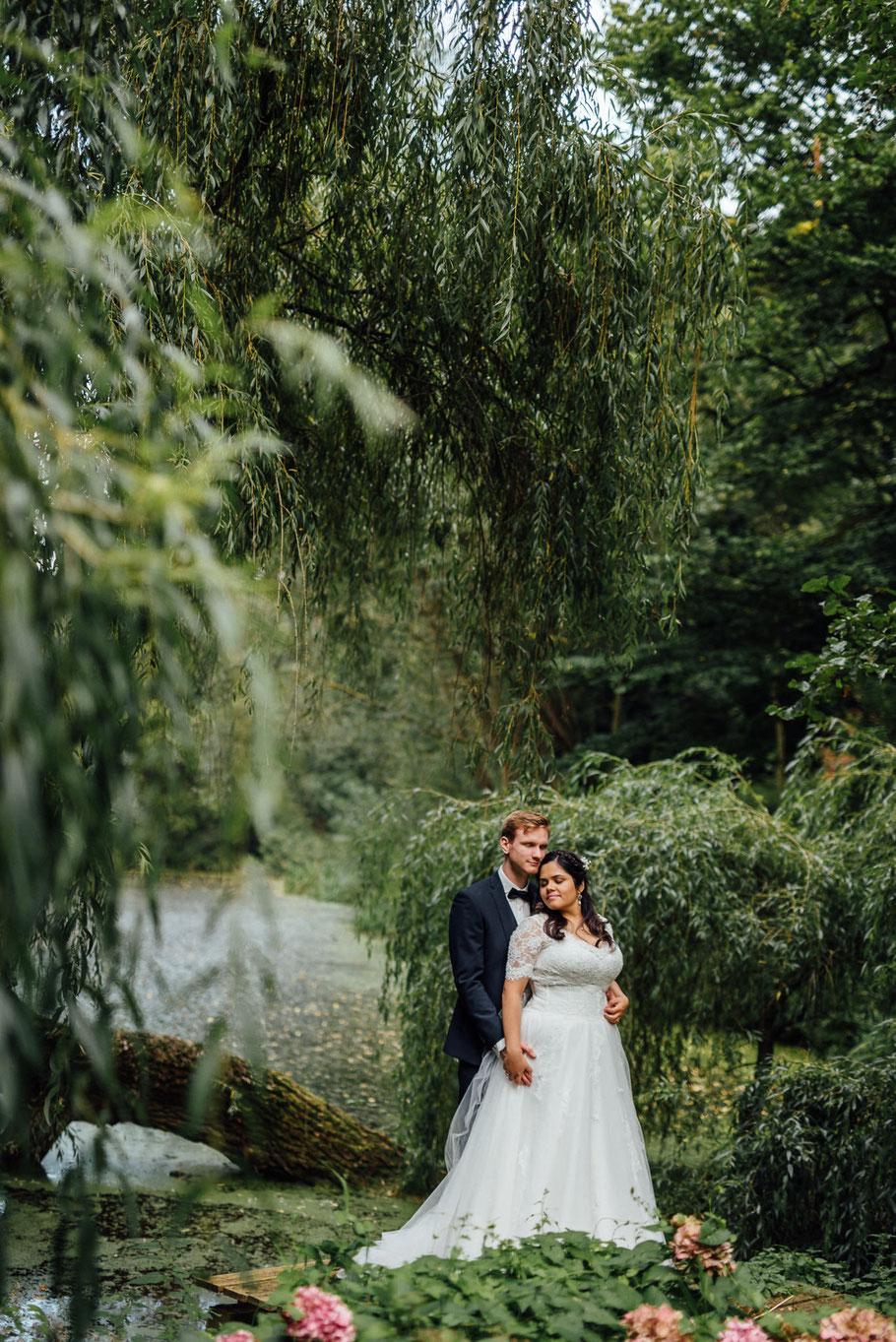 Brautpaar steht hintereinander Wald Linde Tümpel