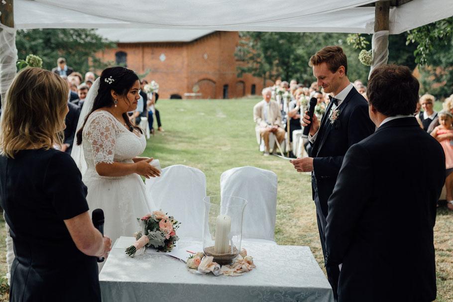 Brautpaar schaut sich während der Trauung an