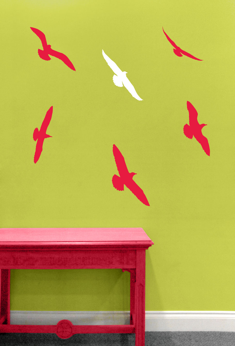 A collection of six pink vinyl sticker seagulls arranged to swoop and soar on a green wall in a living room.