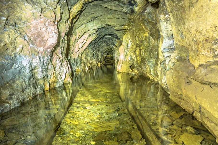 Die Holzschienen sind überflutet vom Wasser im Stollen. Bergbau in Graubünden.