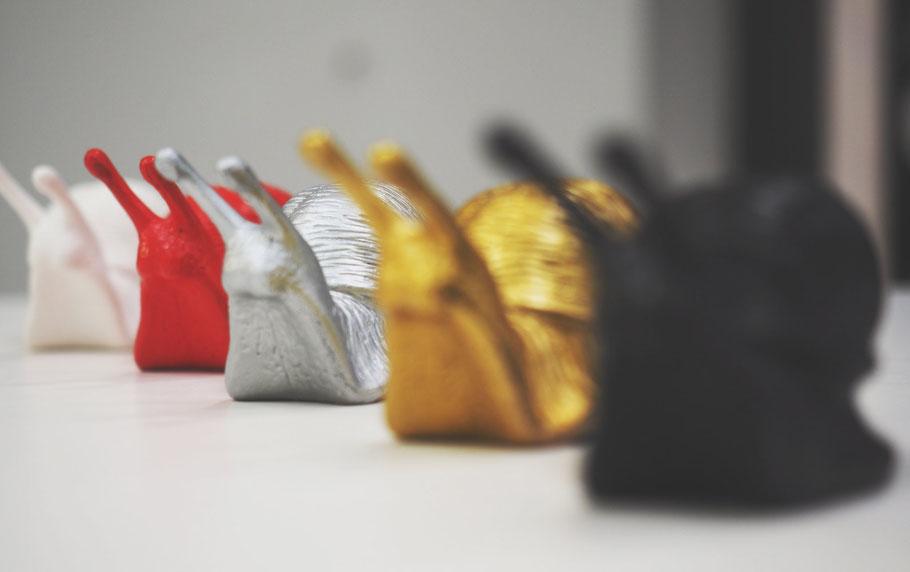 Große Auswahl an Skulpturen von Ottmar Hörl. Auf dem Foto sind die Schnecken in verschiedenen Farben zu sehen.