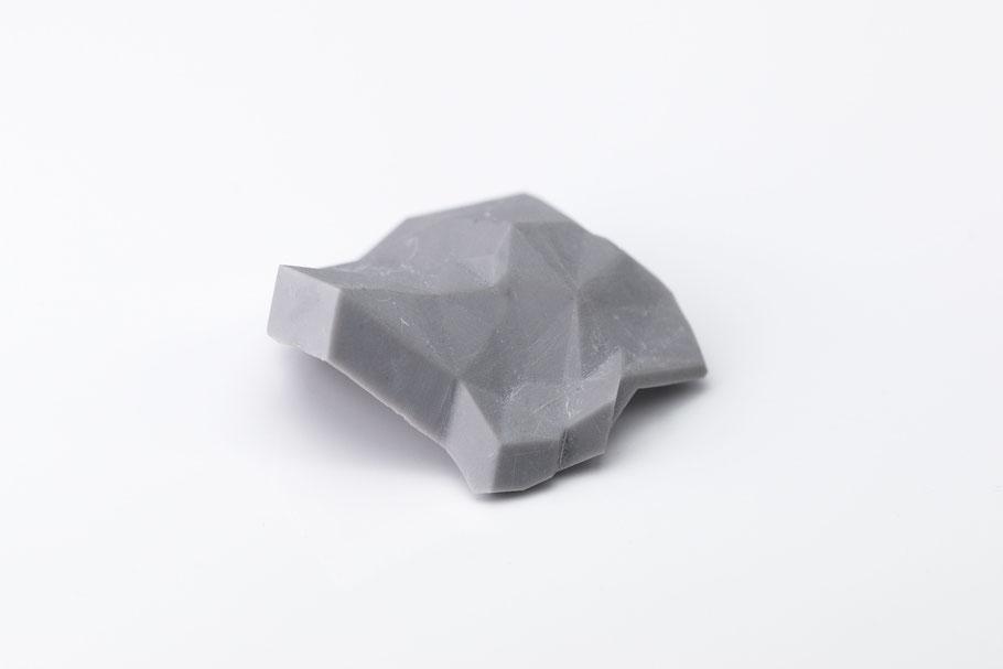 Eine Brosche aus grauem, facettierten Kunststoff