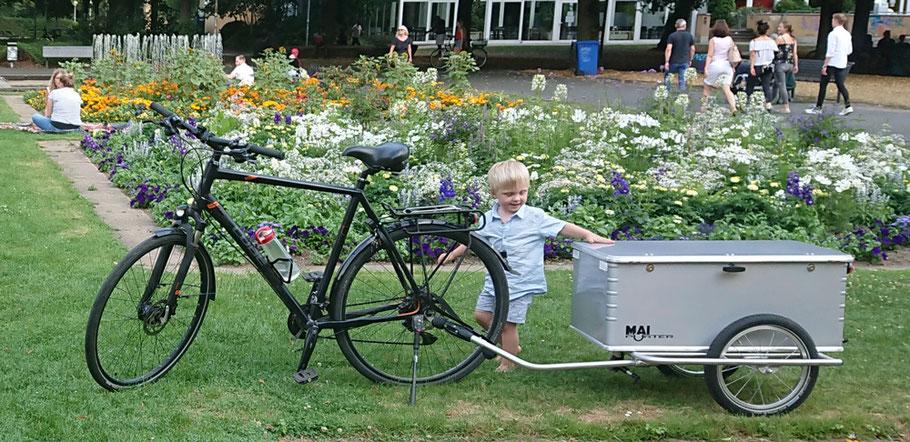 Ein kleiner, blonder Junge steht neben einem Gespann aus Fahrrad und dem Fahrradanhaenger Maiporter Z130 und schaut interessiert auf den Anhaenger
