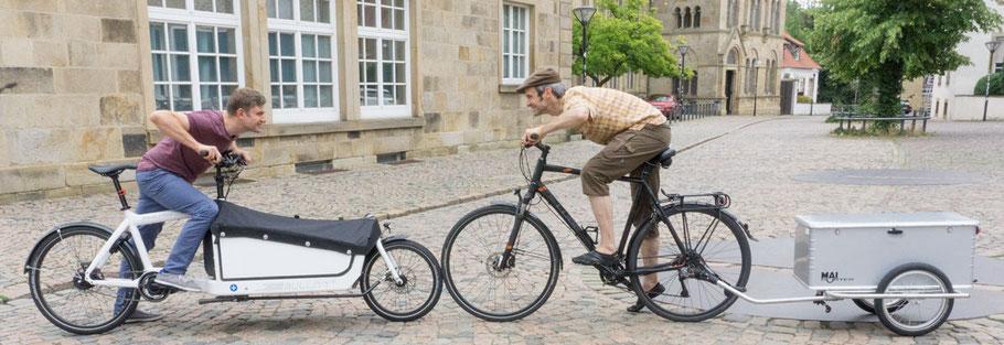 Lastenrad und Gespann aus Fahrrad und Lastenanhaenger stehen Vorderrad an Vorderrad voreinander und tun so, als wollten sie sich gegenseitig wegschieben