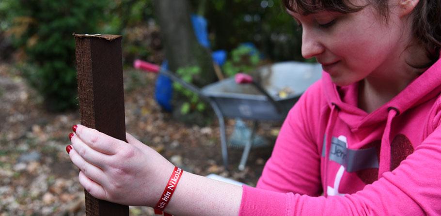 """Jennifer Liebetruth befestigt die Holzstäbe für die neue Kompoststelle in der """"Offenen Tür Nonni"""" in Köln-Ehrenfeld  © Theresa Meier"""