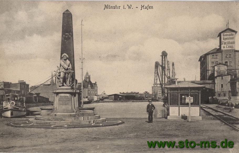 Das imposante Denkmal zeigt einen Seemann mit Südwester, rechts der Flechtheimspeicher, hinten Mitte die Hafenverwaltung