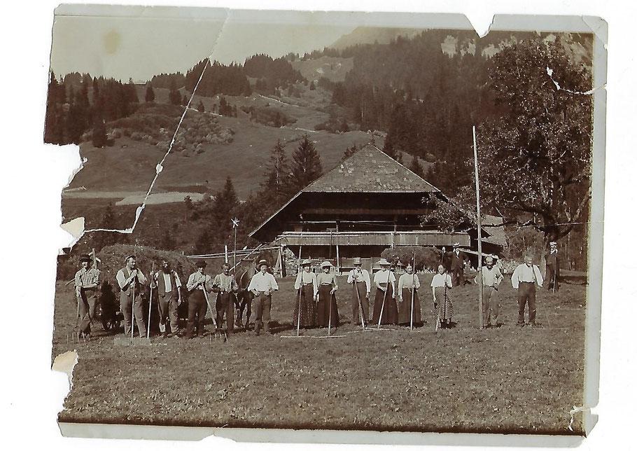 Eine Gruppe von Landwirtschaftlichen Arbeitern beim Heuen vor dem Bauernhof Schwand in Bumbach Schangnau vor über 100 Jahren. Geschichte, Tradition, Nostalgie.